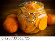 Купить «tangerine jam in a glass jar on a wooden table», фото № 33565725, снято 16 апреля 2020 г. (c) Peredniankina / Фотобанк Лори