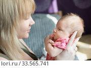 Мама с нежностью смотрит на свою новорожденную дочку. Материнская любовь и забота. Стоковое фото, фотограф Наталья Гармашева / Фотобанк Лори
