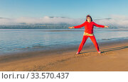 Купить «Beautiful mature woman doing gymnastics on a sandy beach on a background of autumn dawn.», фото № 33570437, снято 7 сентября 2019 г. (c) Акиньшин Владимир / Фотобанк Лори