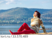 Купить «Beautiful mature woman doing gymnastics on a sandy beach on a background of autumn dawn.», фото № 33570489, снято 8 сентября 2019 г. (c) Акиньшин Владимир / Фотобанк Лори