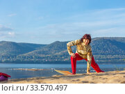 Купить «Beautiful mature woman doing gymnastics on a sandy beach on a background of autumn dawn.», фото № 33570497, снято 8 сентября 2019 г. (c) Акиньшин Владимир / Фотобанк Лори