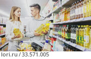 Купить «Portrait of friendly man and woman with shopping cart choosing olive oil in supermarket», видеоролик № 33571005, снято 22 мая 2020 г. (c) Яков Филимонов / Фотобанк Лори