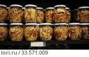Купить «Glass jars with assorted preserved mushrooms on shelves in store», видеоролик № 33571009, снято 5 июля 2020 г. (c) Яков Филимонов / Фотобанк Лори