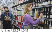 Portrait of woman choosing bottle of champagne and man with beer can in grocery shop. Стоковое видео, видеограф Яков Филимонов / Фотобанк Лори