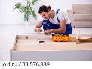 Купить «Young male contractor installing furniture at home», фото № 33576889, снято 11 ноября 2019 г. (c) Elnur / Фотобанк Лори