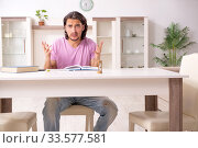 Купить «Young male student preparing for exams at home», фото № 33577581, снято 30 мая 2019 г. (c) Elnur / Фотобанк Лори