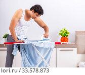 Купить «Young man ironing in the bedroom», фото № 33578873, снято 27 июня 2018 г. (c) Elnur / Фотобанк Лори