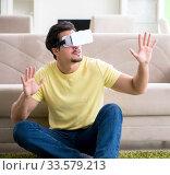 Купить «Young man with virtual reality goggles», фото № 33579213, снято 8 мая 2018 г. (c) Elnur / Фотобанк Лори