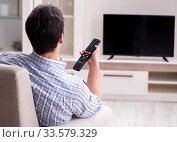 Young man watching tv at home. Стоковое фото, фотограф Elnur / Фотобанк Лори