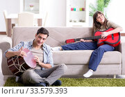 Купить «Young family singing and playing music at home», фото № 33579393, снято 30 января 2018 г. (c) Elnur / Фотобанк Лори