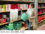 Купить «Woman chooses watering can for watering plants in store», фото № 33580733, снято 7 июня 2020 г. (c) Яков Филимонов / Фотобанк Лори