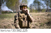 Купить «Tired warrior or military soldier dressed in camouflage, a helmet with goggles, body armor takes off his helmet and ammunition after the battle», видеоролик № 33582225, снято 3 мая 2019 г. (c) katalinks / Фотобанк Лори