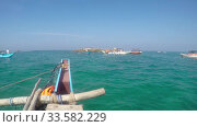 Catamaran fishing wooden boat with rowing control sailing on the waves of the Indian Ocean in Sri Lanka. Стоковое видео, видеограф katalinks / Фотобанк Лори