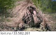 Купить «Invisible camouflaged army military man in camouflage among the grass sniper with an automatic rifle in hands», видеоролик № 33582261, снято 15 мая 2019 г. (c) katalinks / Фотобанк Лори
