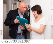 Collector is trying to get the arrears from woman at home door. Стоковое фото, фотограф Яков Филимонов / Фотобанк Лори