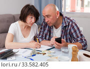 Купить «Husband and wife calculate income and expenses on smartphone», фото № 33582405, снято 27 мая 2019 г. (c) Яков Филимонов / Фотобанк Лори