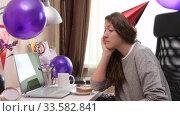 Купить «Woman celebrating birthday from home», видеоролик № 33582841, снято 19 апреля 2020 г. (c) Сергей Петерман / Фотобанк Лори