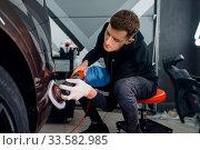 Купить «Male worker polishes bumper, car detailing», фото № 33582985, снято 20 марта 2020 г. (c) Tryapitsyn Sergiy / Фотобанк Лори