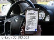 Купить «Водитель держит смартфон с полученным цифровым пропуском для передвижения по городу. Пандемия коронавируса COVID-19 в Москве», эксклюзивное фото № 33583033, снято 17 апреля 2020 г. (c) Щеголева Ольга / Фотобанк Лори