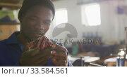 Mixed race man holding hand-made ball in factory. Стоковое видео, агентство Wavebreak Media / Фотобанк Лори