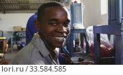 Mixed race worker smiling in factory. Стоковое видео, агентство Wavebreak Media / Фотобанк Лори