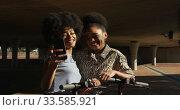 Купить «Two mixed race women taking picture under bridge», видеоролик № 33585921, снято 17 мая 2019 г. (c) Wavebreak Media / Фотобанк Лори