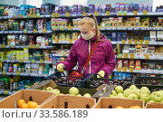 Купить «Woman in protective mask and gloves buys fruit in a supermarket during an outbreak of coronavirus», фото № 33586189, снято 17 апреля 2020 г. (c) Евгений Харитонов / Фотобанк Лори