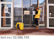 Купить «Courier of an online food delivery service calls up a customer in front of a closed door during quarantine in connection with the COVID-19 epidemic», фото № 33586193, снято 19 апреля 2020 г. (c) Евгений Харитонов / Фотобанк Лори