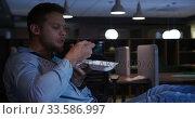 Купить «Businessman eating in a modern office by night», видеоролик № 33586997, снято 29 мая 2019 г. (c) Wavebreak Media / Фотобанк Лори