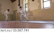 Купить «Fencer athletes during a fencing training in a gym», видеоролик № 33587741, снято 16 ноября 2019 г. (c) Wavebreak Media / Фотобанк Лори