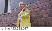 Купить «Mixed race woman standing on street», видеоролик № 33588017, снято 10 января 2020 г. (c) Wavebreak Media / Фотобанк Лори