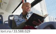 Купить «Mixed race woman taking the bus and reading a book», видеоролик № 33588029, снято 10 января 2020 г. (c) Wavebreak Media / Фотобанк Лори
