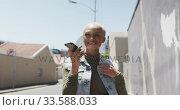Купить «Mixed race woman on the phone on the street», видеоролик № 33588033, снято 10 января 2020 г. (c) Wavebreak Media / Фотобанк Лори