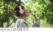 Купить «Mixed race woman listening music on the street», видеоролик № 33588513, снято 23 февраля 2020 г. (c) Wavebreak Media / Фотобанк Лори