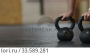 Side view athletic Caucasian woman holding kettlebell weights. Стоковое видео, агентство Wavebreak Media / Фотобанк Лори
