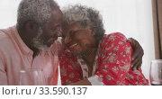 Купить «A senior african american couple spending time together at home  social distancing in quarantine.», видеоролик № 33590137, снято 12 ноября 2019 г. (c) Wavebreak Media / Фотобанк Лори