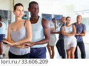 Купить «Young smiling people practicing passionate samba in dance class», фото № 33606209, снято 30 июля 2018 г. (c) Яков Филимонов / Фотобанк Лори