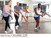 Купить «Cheerful people practicing vigorous lindy hop movements in dance class», фото № 33606225, снято 30 июля 2018 г. (c) Яков Филимонов / Фотобанк Лори