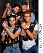 Group of friends playing laser tag game with laser guns in dark labyrinth. Стоковое фото, фотограф Яков Филимонов / Фотобанк Лори