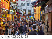 Dense crowd of tourists walking in a narrow street in the historic district of Macau, China. Редакционное фото, фотограф Leonid Serebrennikov / age Fotostock / Фотобанк Лори