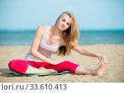 Купить «Young lady practicing yoga. Beautiful woman posing at the summer sand beach. Workout near ocean sea coast. Beautiful fit tan girl. Fitness model caucasian...», фото № 33610413, снято 1 июня 2020 г. (c) easy Fotostock / Фотобанк Лори