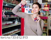 Smiling woman customer deciding on nail polish. Стоковое фото, фотограф Яков Филимонов / Фотобанк Лори