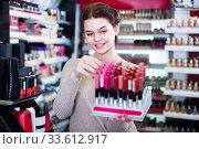 Купить «Young customer is searching for reliable lipstick», фото № 33612917, снято 21 февраля 2017 г. (c) Яков Филимонов / Фотобанк Лори