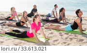 Купить «Sporty people practicing yoga on beach», фото № 33613021, снято 14 июня 2017 г. (c) Яков Филимонов / Фотобанк Лори