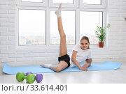 Девочка выполняет растяжку мышц ноги выполняя упражнения дома. Стоковое фото, фотограф Иванов Алексей / Фотобанк Лори