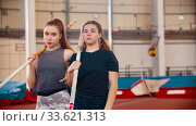 Pole vault training - two women standing on the stadium holding poles and looking in the camera. Стоковое фото, фотограф Константин Шишкин / Фотобанк Лори