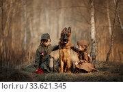 Постановочный портрет девочек в военной форме с немецкой овчаркой. Стоковое фото, фотограф Julia Shepeleva / Фотобанк Лори