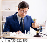 Купить «Young lawyer playing chess to train his court strategy and tacti», фото № 33622193, снято 31 июля 2018 г. (c) Elnur / Фотобанк Лори