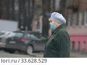 Женщина в маске на Крупской улице в Балашихе в дни пандемии коронавируса COVID-19 (2020 год). Редакционное фото, фотограф Дмитрий Неумоин / Фотобанк Лори