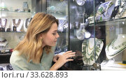 Portrait through glass of young woman choosing necklace in jewelry store. Стоковое видео, видеограф Яков Филимонов / Фотобанк Лори